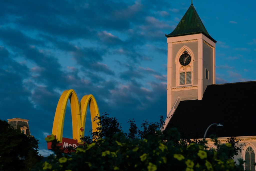 A photograph of Mcdonalds Sign and Church Morning Light